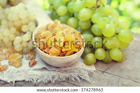 Dried yellow raisins in wooden spoon with fresh ripe grapes