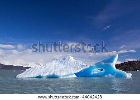 Drifting blue iceberg on a sky with clouds background and stone mountains.