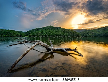 Driftwood at sunset reflects in the calm waters of this Appalachian Mountain lake in Kentucky - stock photo