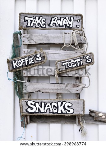 Driftwood signboard of a beach club with coffee and Drinks to go. Close-up of wooden signboards at a beach club.