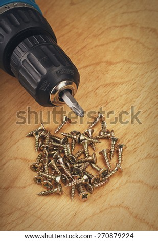 drill and large screws on a wood background - stock photo