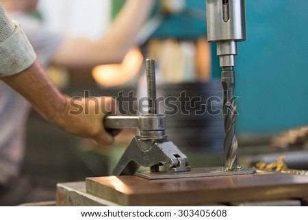 Drilling hole in metal sheet with auger in factory workshop during man worker fixing workpiece with clamp equipment - stock photo