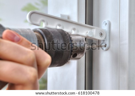 Drilling holes for fasteners to install the window limiter close-up. & Installer Hands Closeup Installation Limiter Pvc Stock Photo ... pezcame.com