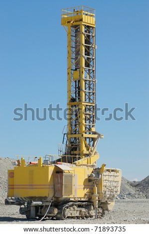 Drilling machine in open cast mining quarry - stock photo