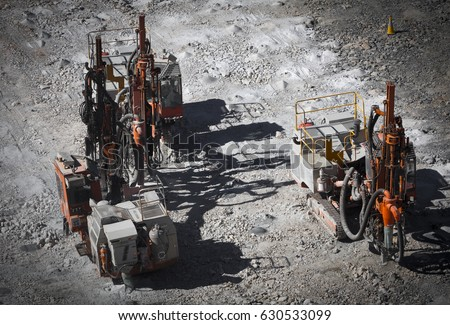Drilling machine makes bore holes for explosives in open cast mine. Galaxy Lithium Mine in Western Australia. Spodumene ore from the open cast mine.