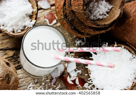 Drink coconut milk in glass with straw, organic protein cocktail selective focus - stock photo