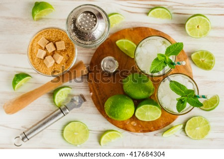 Drink making tools and ingredients for cocktail on wooden background. Mojito, steatite. View from above. - stock photo