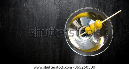 Drink martini. Martini with olives on a black table. Free space for text. Top view - stock photo