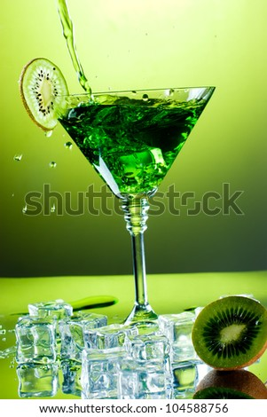 Drink pouring into martini glass