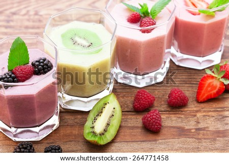 Drink smoothies summer strawberry, blackberry, raspberry on wooden table.