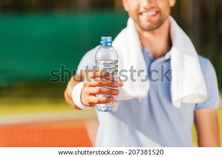 Drink some water! Close-up of happy young man in polo shirt and towel on shoulders stretching out bottle with water while standing on tennis court  - stock photo