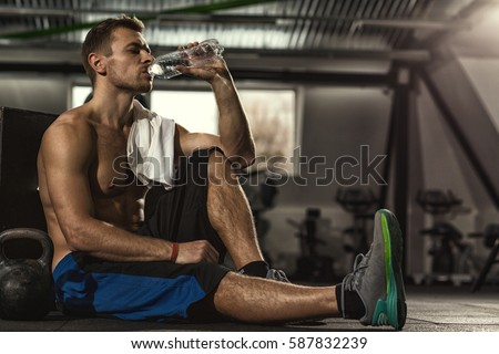 Drink water shirtless sportsman resting after stock photo drink water shirtless sportsman resting after training at the gym sitting on the floor drinking sciox Choice Image