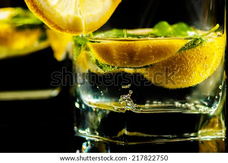 Drink water with lemon and mint on reflect background - stock photo