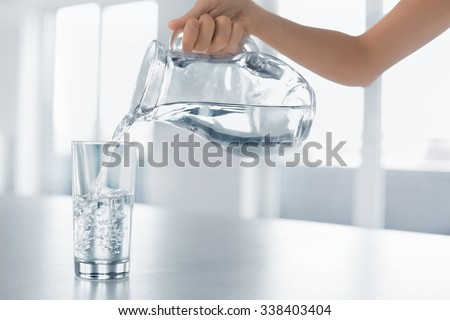Drink Water. Woman's Hand Pouring Fresh Pure Water From Pitcher Into A Glass. Health And Diet Concept. Healthy Lifestyle. Healthcare And Beauty. Hydratation. - stock photo