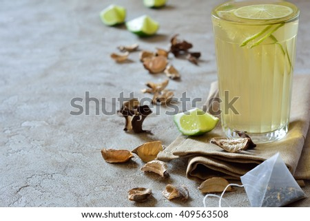 Drink with lime in a glass on a black table - stock photo