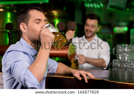 Drinking a freshly tapped beer. Handsome young man drinking beer while bartender tapping beer on the background - stock photo