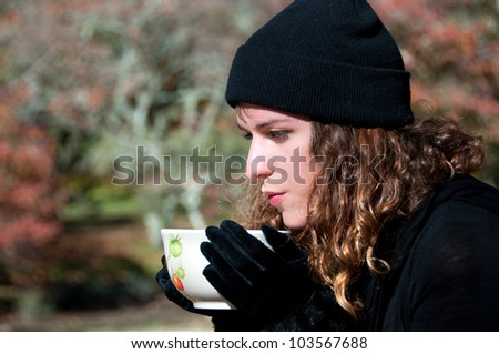 Drinking a hot cup of soup or coffee or tea  in the park in autumn - stock photo