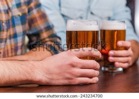 Drinking beer at the bar. Close-up of two friends drinking beer at the bar counter  - stock photo