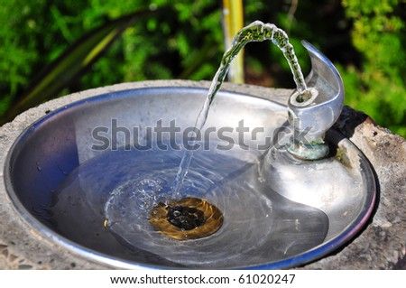 Drinking fountain with flowing water. - stock photo