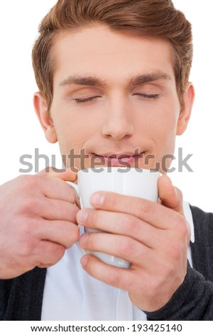 Drinking fresh coffee. Handsome young man holding cup of coffee and keeping eyes closed while standing isolated on white - stock photo