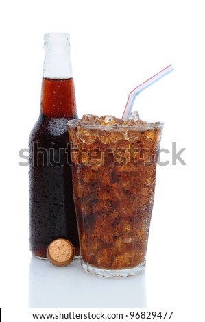 Drinking glass filled with ice cubes and cola soda with an open bottle tucked in behind over a white background. - stock photo