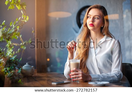 Drinking latte. Young beautiful long hair woman holding cup of coffee while sitting at cafe.