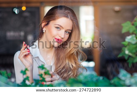 Drinking latte. Young beautiful long hair woman holding cup of coffee while sitting at cafe. - stock photo