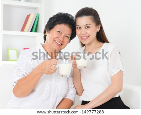 Drinking milk. Happy Asian family drinking milk at home. Beautiful senior mother and adult daughter, healthcare concept. - stock photo