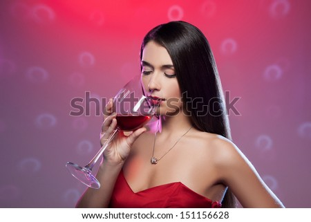 Drinking red wine. Beautiful young woman in red dress holding a glass with wine while standing isolated on colored background