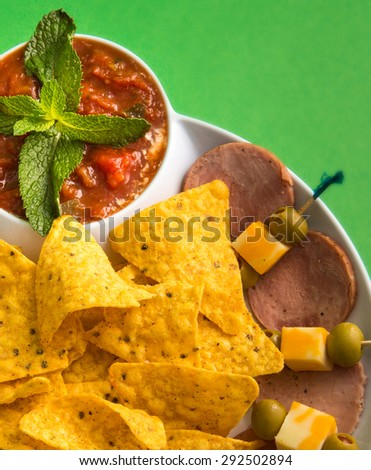 Drinking snack: Spicy mexican nachos over a green background. Delicious junk food. Special for a snack while drinking beer