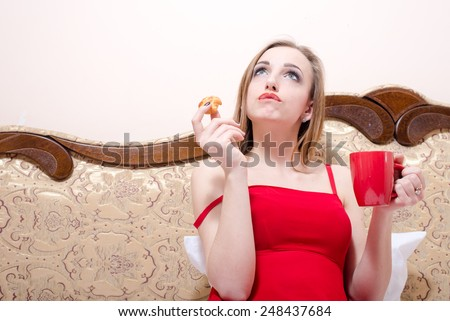 drinking tea and eating cake beautiful blonde young woman having fun looking up at copy space closeup portrait  - stock photo