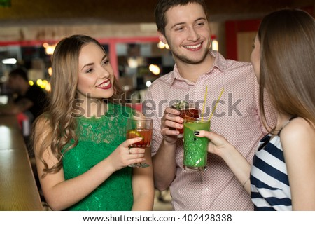 Drinking unites. Three young attractive people drinking and having conversation.