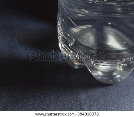 Drinking water bottle with blue color cap made from transparent food grade plastic put on the black color leather background represent the water containing material related.  - stock photo