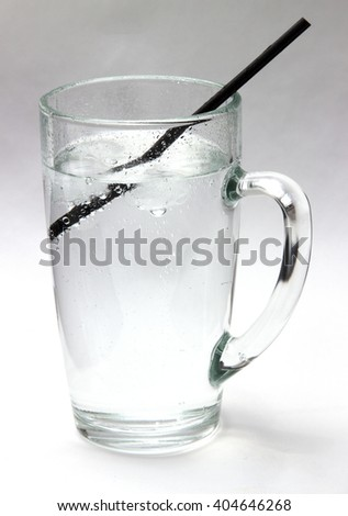 Drinking water. Daily drink a glass of very cold water, life giving water. Crystal clear water with ice in a transparent glass on a white background.  - stock photo