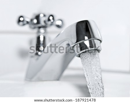drinking water flows from a chrome water tap. - stock photo