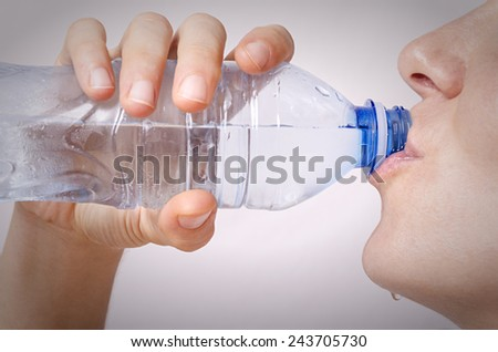 Drinking water. Selective focus on bottle. - stock photo