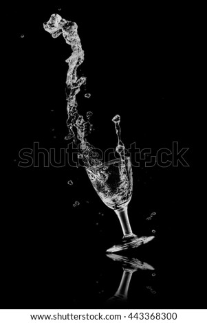drinking water splash out of glass on a black background.