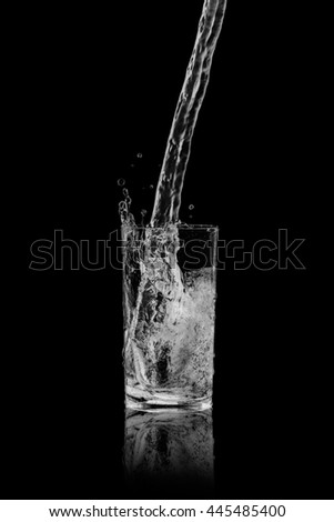 drinking water splash out of glass on black blackground.
