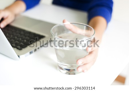Drinking water while working with laptop computer - stock photo