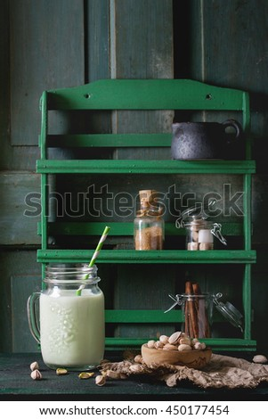 Drinking yogurt with pistachios served in glass mason jar with cocktail tubes and bowl of nuts on old wooden table and rack with spices at background . Dark rustic style. - stock photo