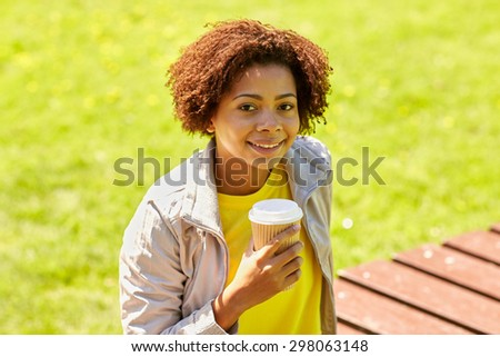 drinks and people concept - smiling african american young woman or teenage girl drinking coffee from paper cup outdoors