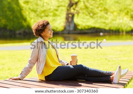drinks and people concept - smiling african american young woman or teenage girl drinking coffee from paper cup at summer park  - stock photo