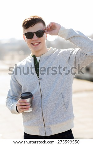 drinks and people concept - smiling young man or teenage boy drinking coffee from paper cup outdoors - stock photo