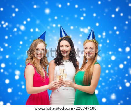 drinks, christmas, winter holidays, people and celebration concept - smiling women in party hats with glasses of sparkling wine over blue snowing background - stock photo