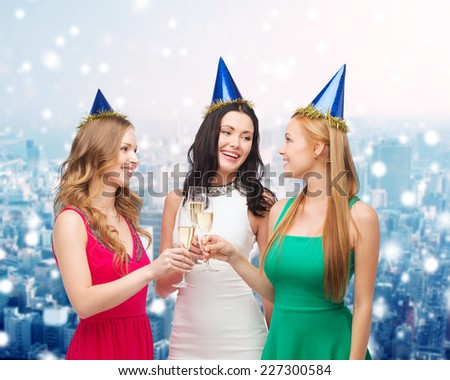 drinks, christmas, winter holidays, people and celebration concept - smiling women in party hats with glasses of sparkling wine over snowy city background - stock photo