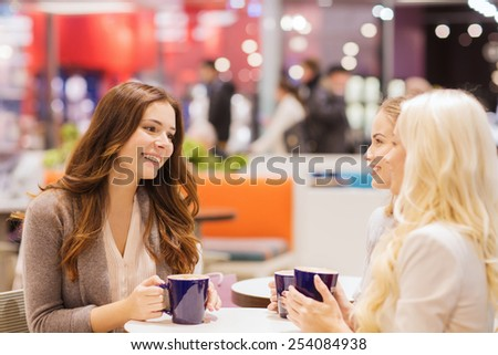 drinks, communication, friendship and people concept - happy young women with coffee cups sitting at table and talking in mall or cafe - stock photo