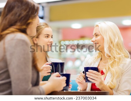 drinks, communication, friendship and people concept - happy young women with cups sitting at table and talking in mall or cafe - stock photo