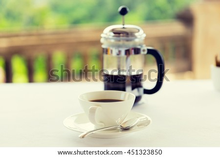 drinks, energetic, morning and caffeine concept - cup of black coffee and french press on table at restaurant - stock photo
