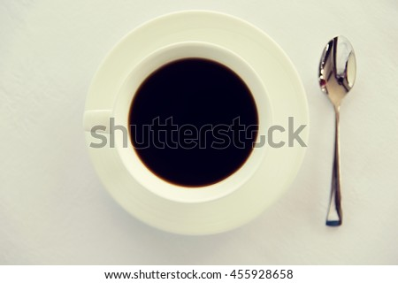 drinks, energetic, morning and caffeine concept - cup of black coffee with spoon and saucer on table - stock photo