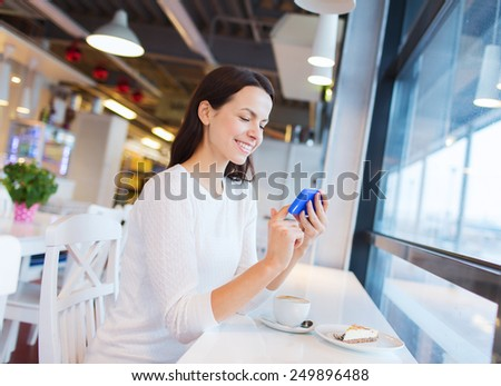 drinks, food, people, technology and lifestyle concept - smiling young woman with smartphone drinking coffee at cafe - stock photo